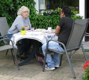 Zwei Personen sitzen auf Stühlen in einem Garten und unterhalten sich.