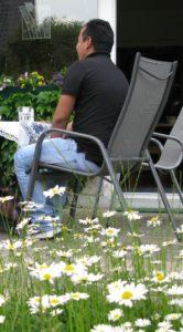 Tendar sitzt auf einem Stuhl in einem Garten.
